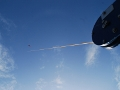 The kite is small compared to the blade of a wind turbine and flies very high